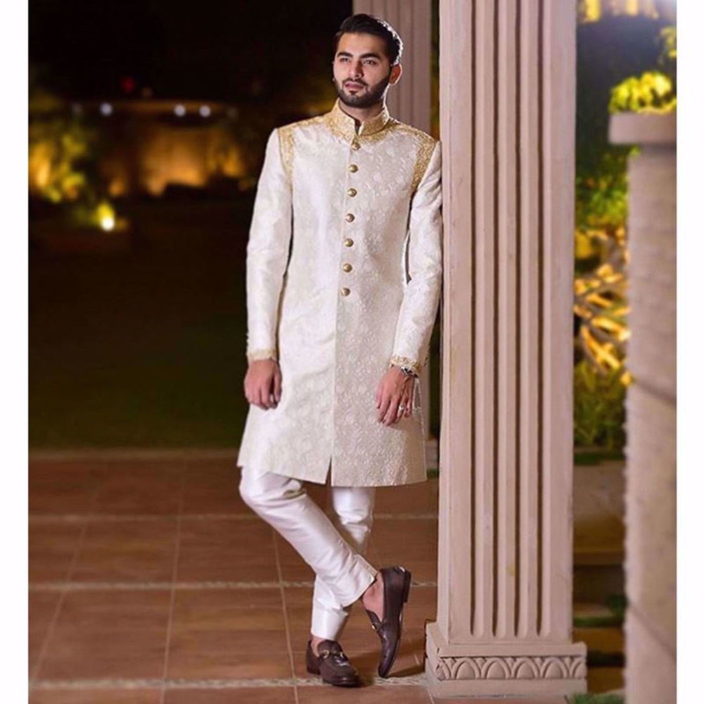 Picture of SHEHROZE HANIF IN A WHITE ON WHITE EMBROIDERED CLASSIC TAILORED SHERWANI WITH GOLD ZARDOZI COLLAR