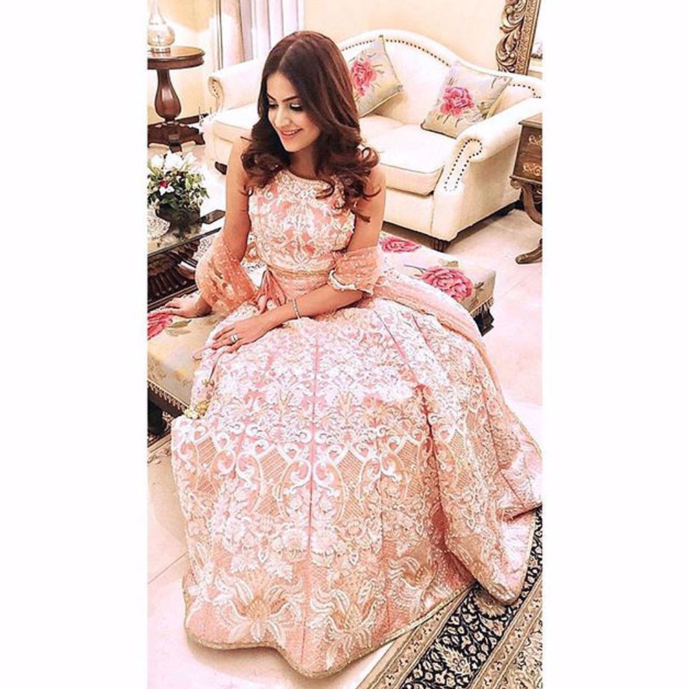 Picture of Alicia brings out the true glow that every @NomiAnsari customer has  A beautiful peachy pink lehnga cholli is the perfect pick this season