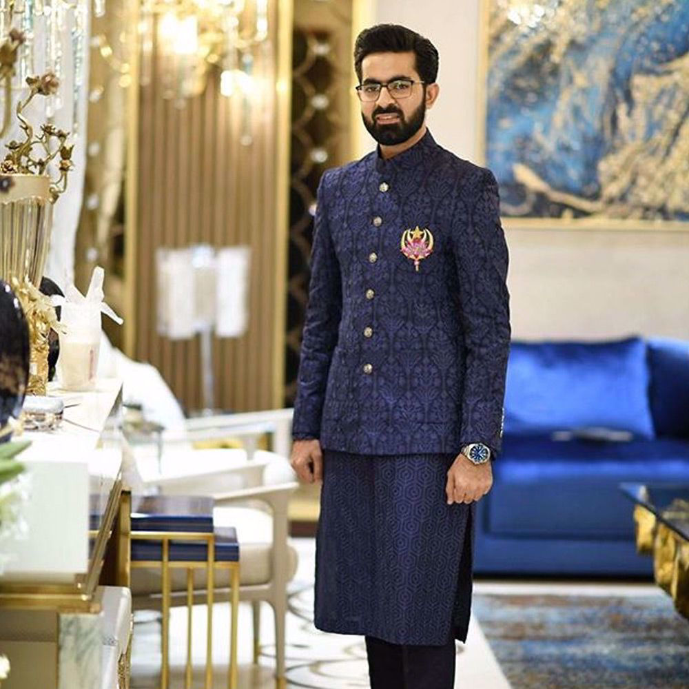 Picture of Ahsan Rafiq in a tailored midnight blue embroidered prince coat with a midnight kurta and straight pants at his pre wedding dinner.