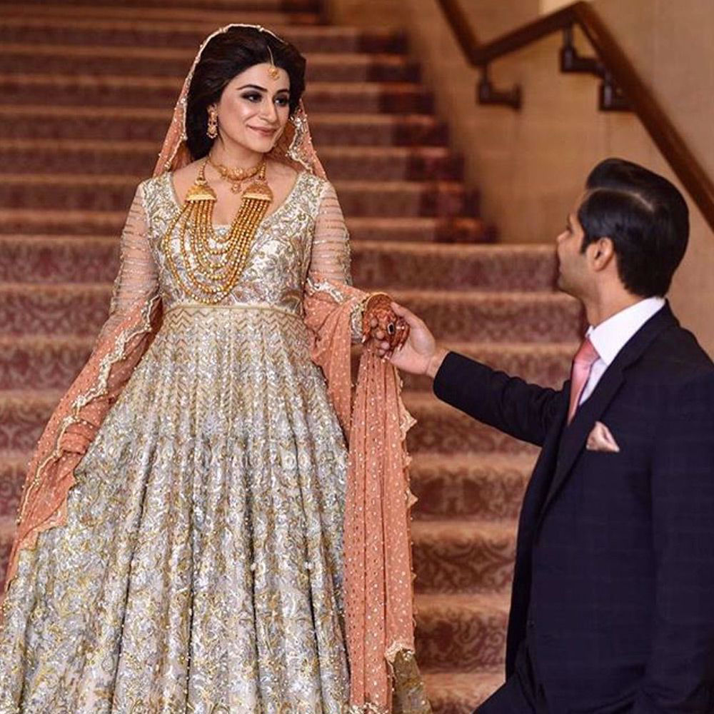 Picture of Manal Shafqat wears an ivory Anarkali paired with a paneled skirts and a peach tulle net dupatta