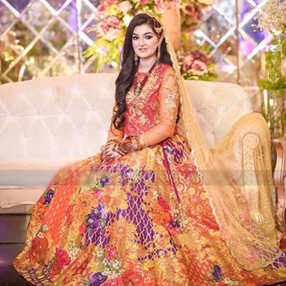 Picture of Our beautiful client Rida Shafqat sparkles in a custom made mehndi bridal that blends together vibrant hues of rust, orange and coral.