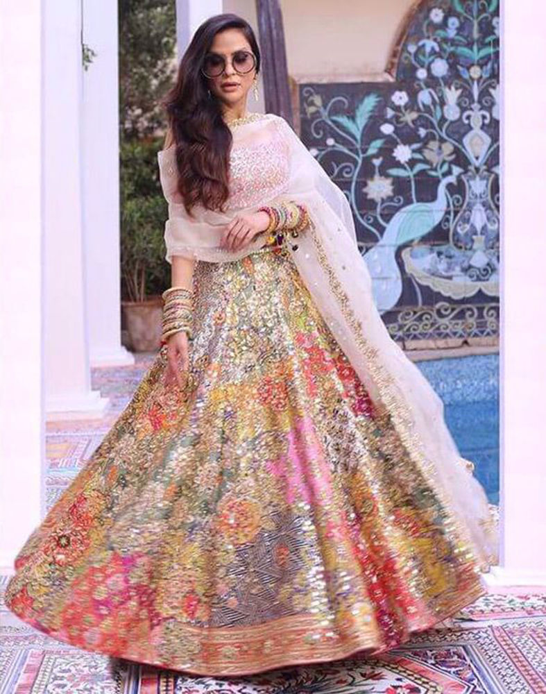 Picture of A multi-hued print with the most dazzling mirrorwork and hand detailing, paired with a pink mirror-worked choli and minimal ivory scalloped dupatta