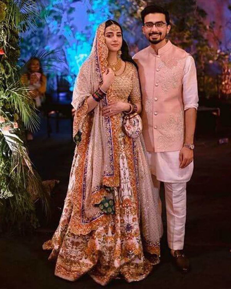 Picture of A soft gold choli paired with our signature print and handworked lehnga, plus a detailed bordered dupatta in ivory for Zarmina's classy bridal look