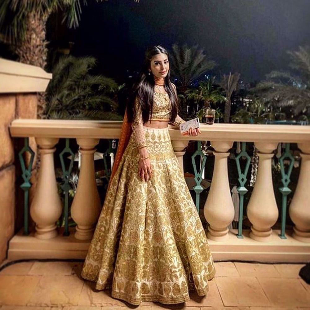 Picture of Iman Baig spotted wearing an ivory and Gold lehenga by #nomiansari at a recent #wedding in #dubai