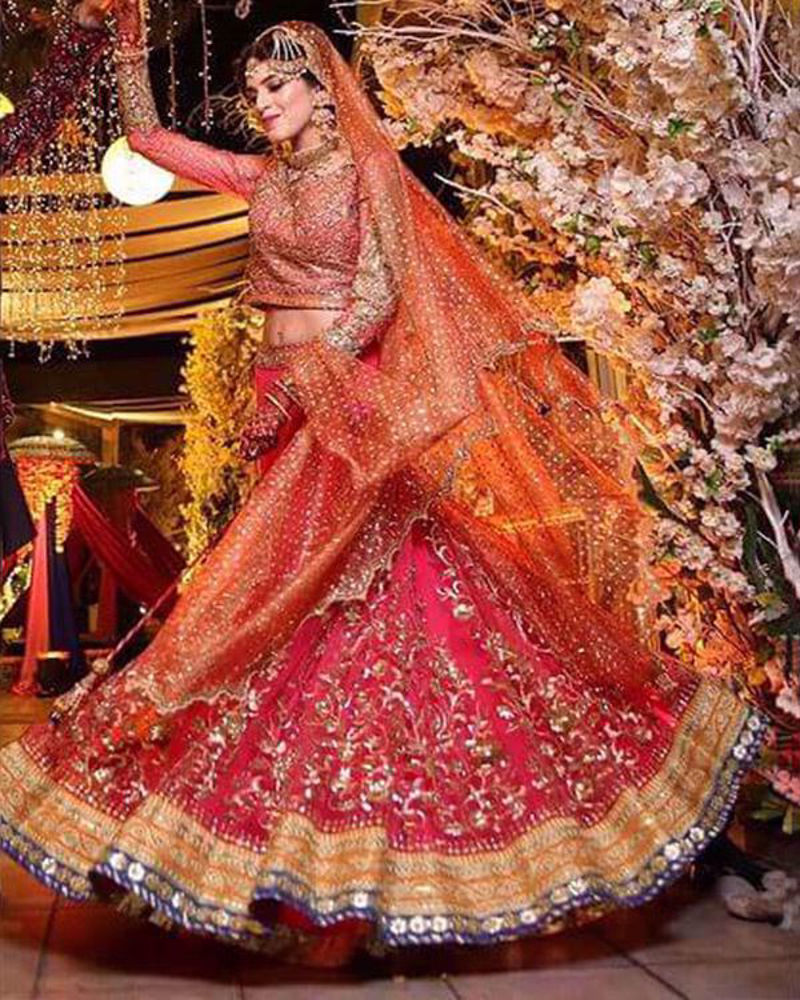 Picture of Manal wears our customized mehndi bridal in bright pink with intricate gold embellishments and a peach net dupatta