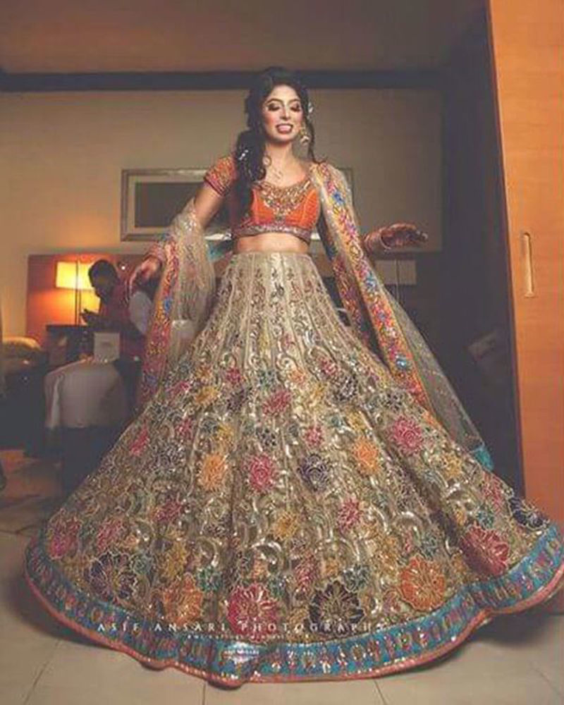 Picture of Sudha Hemani makes a beautiful bride in our floral embellished lehnga, paired with a bright orange choli and intricately bordered dupatta for her mehndi