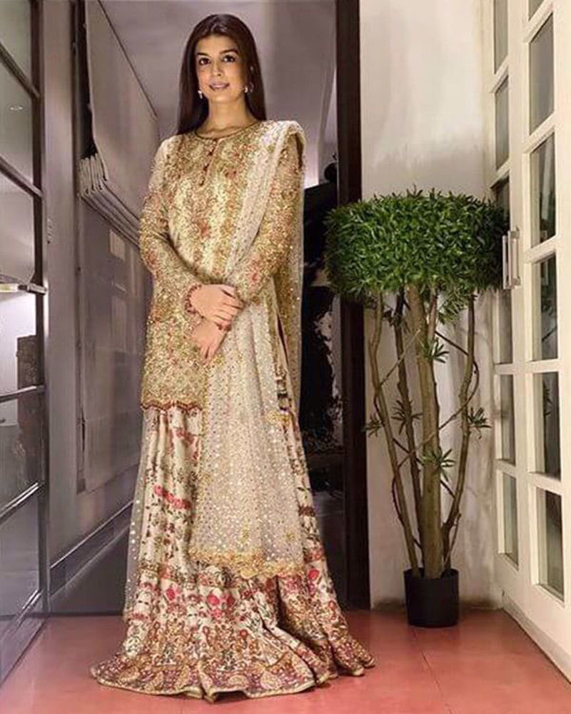 Picture of Zainab Cheema wears a dhakka pyjama and shirt in ivory and gold with kundun details, and a touch of reds and pinks.